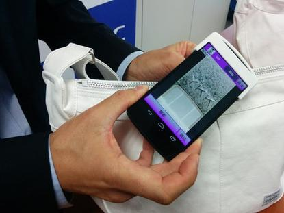 """An NEC staffer demonstrates an anti-counterfeiting smartphone app on Monday in Tokyo. The """"object fingerprint"""" technology can compare smartphone photos of minute manufacturing patterns in metal and plastic objects and compare them with a database to establish their origins and authenticity."""