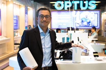 Optus managing director for networks, Dennis Wong, with the 5G fixed wireless device used in the telco's 5G New Radio trial