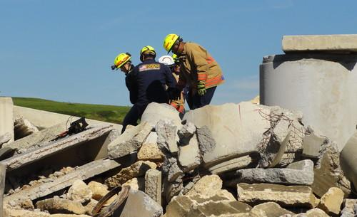 "Rescue workers with the Fairfax County (Virginia) Fire and Rescue Department pull a buried ""victim"" out of rubble after using a new technology called FINDER developed by NASA and the U.S. Department of Homeland Security."