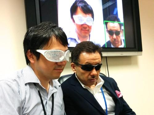 Staffers at the National Institute of Informatics in Tokyo on August 11, 2015, show how a facial recognition system can identify someone wearing sunglasses (right) but not someone wearing the Privacy Visor (left), developed at the institute.