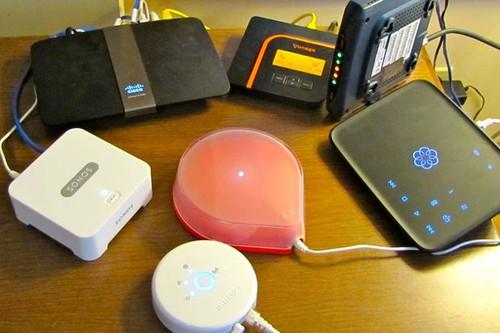 The Revolv hub (center) works with a variety of smart devices. Clockwise, from bottom center: Philips Hue Personal Wireless Lighting bridge; Sonos Play:1 streaming music system; Cisco LInksys router; Vonage V-Portal VoIP hub