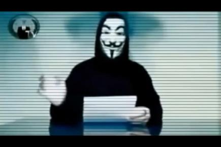 The statement is fronted by a figure wearing Anonymous' signature Guy Fawkes mask, read aloud by a male text-to-speech synthesiser.